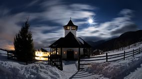 Transylvania monastery in the cold winter night with full moon. Snow and clouds royalty free stock photo