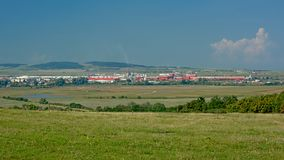 Transylvanian fields with city, industrial buildings and mountains in the background. Transylvanian landscape with green fields with and a city, industrial royalty free stock photo