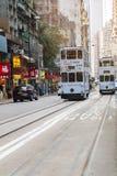 Tranvía blanca del autobús de dos pisos del color en una calle muy transitada en el distrito pálido de Sheung de Hong Kong Island fotos de archivo