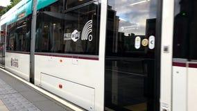 Tranvía de Edimburgo de Escocia que llega una parada durante el día almacen de video