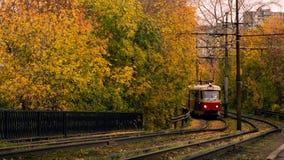 Tranvía en el fondo de los árboles del otoño Fotos de archivo