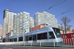 Tranvía inminente con las construcciones de viviendas en el fondo, Dalian, China Imagenes de archivo
