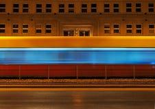 Tranvía que pasa el edificio del paisaje de la noche del fondo Imágenes de archivo libres de regalías