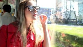 Tranvía rubia joven del montar a caballo de la mujer, ajustando su pelo y vidrios metrajes