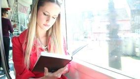 Tranvía rubia joven del montar a caballo de la mujer, libro de lectura el día soleado metrajes