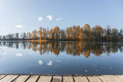 Trap at lake. Sunny autumn day at lake. coloured trees with reflection in a lake Stock Image