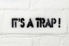 It is a trap. It's a trap exclamation stencil print on the white brick wall Royalty Free Stock Photography