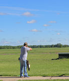 Trap Shooting. A young trap shooter shooting and hitting a clay pigeon stock images