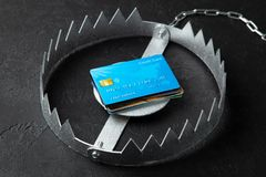 Trap with stack of credit cards. Unsafe credit risk. Black background.