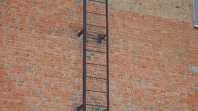Trap van metaal op bakstenen muurachtergrond Beweging omhoog De voorgevel van brandtrapomhelzingen stock video
