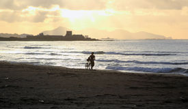 Trapani and the beach at sunset. Man walks on the beach with bicycle Stock Photos