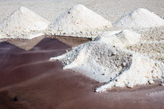 Trapani saltworks, salt pile and red water for algal concentrations. Water in saltworks is red for presence of micoorganism, the color indicates the salinity of Stock Images