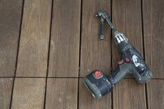 Trapano elettrico lasciato sul pavimento di legno Fotografia Stock