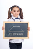 Trapezoid. 8 year old school girl with chalkboard displaying a trapezoid shape on white background Stock Images