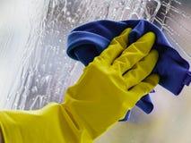 Trapo con guantes y espray de la ventana de la limpieza de la mano Fotografía de archivo libre de regalías