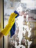 Trapo con guantes y espray de la ventana de la limpieza de la mano Imagenes de archivo