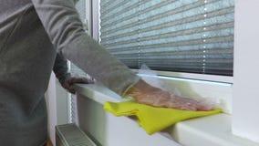 Trapo del amarillo del uso de la mujer para la limpieza del travesaño de la ventana almacen de metraje de vídeo