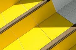 trappa av keramiska tegelplattor av varm guling som är upplysta vid solen med gjorda mörkare hörn Royaltyfri Foto