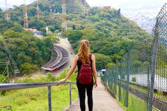 Trappa för ryggsäck för ung turist- flicka bärande stigande ned och tycka om sikten från det Jaragua maximumet, Brasilien arkivbilder