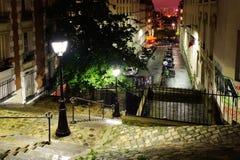 Trappa, ljus och historiska byggnader på Montmartre vid natt Fotografering för Bildbyråer