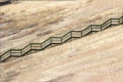 Trappa och staket i ett fält arkivbilder
