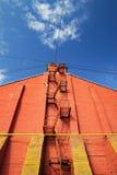 Trappa på väggen för röd tegelsten på klar blå himmel Arkivbild