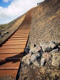 Trappa till krater med folk överst som klättrar trappan arkivbild