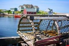 Trappe de langoustine et village de pêche Photo stock