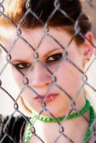 Trapped. Serious teen trapped behind a chain link fence Stock Photography