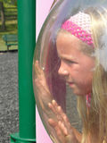 Trapped. A young girl looks like she is trapped behind a plastic dome window at a park Royalty Free Stock Image