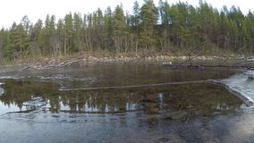 Trapped air under clear river shore ice with moving water. And forest background stock video footage