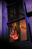 Trapped. Bloody hand behind a window, of a trapped and tortured man  inside a house enlighted by candles Stock Images