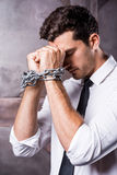 Trapped in chains. Side view of frustrated young man in shirt and tie touching his forehead with hands trapped in chains Royalty Free Stock Photo
