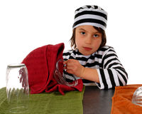 Trapped by Chores. Unhappy elementary child in striped prison garb drying dishes Stock Images