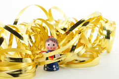 Trapped by Christmas. Small girl ornament surrounded by gold ribbon isolated on white Stock Image