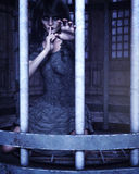 Trapped 3d CG. Caged Gothic woman with stitched lips background Stock Photos