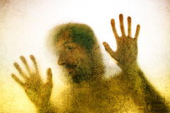 Trapped man, back lit silhouette of hands behind matte glass Royalty Free Stock Photos