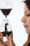 Trapped in sand timer. Woman holding up a hour glass sand timer watching herself trapped in there Stock Photography