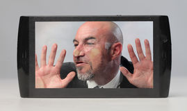 Trapped in technology. Businessman with his head squashed against a tablet screen Stock Photography