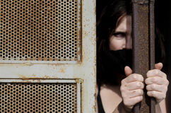 Trapped Woman. A woman trapped in a prison jail cell with a mouth cover Royalty Free Stock Photos