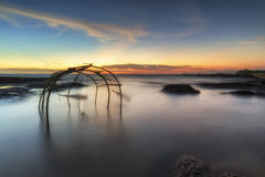 Trappole del pesce disposte lungo la spiaggia La spiaggia crepuscolare Immagine Stock