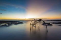 Trappole del pesce disposte lungo la spiaggia La spiaggia crepuscolare Fotografie Stock