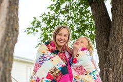 Trapunta avvolta due ragazze Fotografia Stock
