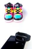 Traqueur et smartphone de forme physique près des espadrilles multicolores D'isolement Images stock