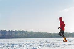 Trascini il corridore di corsa che porta gli abiti sportivi protettivi rossi sul corso di formazione dell'inverno all'aperto Immagini Stock