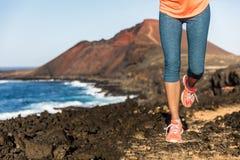Trascini le gambe e le scarpe correnti del corridore della donna dell'atleta Immagini Stock