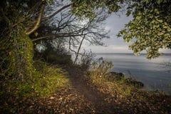 Trascini sulla spiaggia con le nuvole tempestose e sul mare grigio nei precedenti fotografia stock
