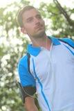 Trasduttore auricolare d'uso dell'uomo sportivo a musica d'ascolto durante pareggiare Fotografia Stock