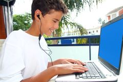 Trasduttori auricolari felici del computer portatile del ragazzo dell'allievo dell'adolescente Fotografia Stock