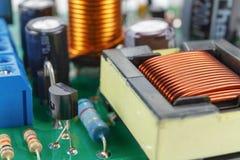 Trasformatore e componenti elettronici installati su un primo piano del circuito stampato immagini stock